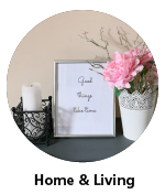Candle in candleholder, picture frame with text-based artwork and metal vase with pink flower